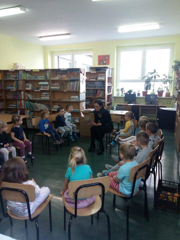 Pani z biblioteki szkolnej czyta dzieciom bajkę