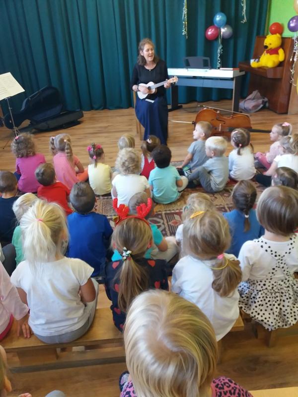 Zdjęcie dzieci słuchających pani grającej na różnych instrumentach