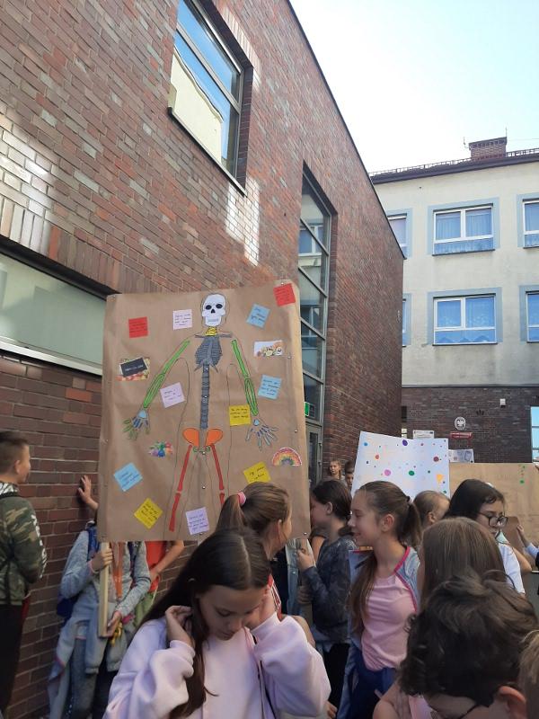 Zdjęcie uczniów przed budynkiem szkoły
