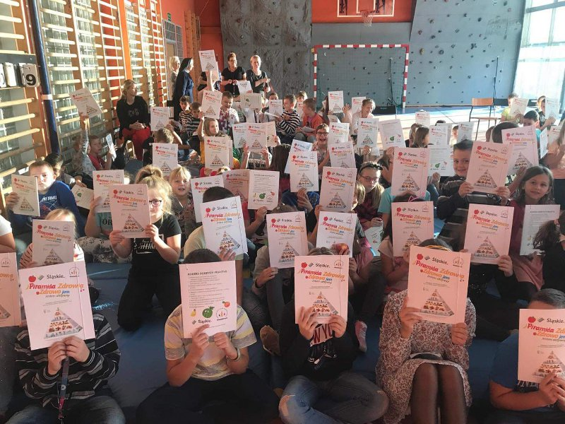 Dzieci w sali gimnastycznej trzymające informację o piramidzie zdrowia